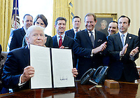 United States President Donald Trump, flanked by business leaders, signs executive order establishing regulatory reform officers and task forces in US agencies in the Oval Office of the White House on February 24, 2017 in Washington, DC. Photo Credit: Olivier Douliery/CNP/AdMedia
