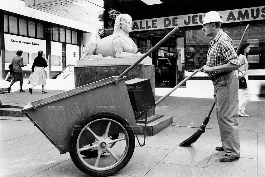 Switzerland. Geneva. Garbage collectors. Streets cleaning. A street sweeper and his cart near the statue of an egyptian sphinx, the creature with a human head and a lion's body. The name 'sphinx' which means 'strangler' was first given by the Greeks to a fabulous creature which had the head of a woman and the body of a lion. Union de Banques Suisses is now called Union Bank of Switzerland (UBS). © 1991 Didier Ruef