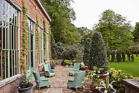 The red brick orangery opens onto a terrace furnished with four wicker wing-backed armchairs