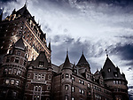 Low angle view of Fairmont Le Château Frontenac castle rooftops in twilight with dark stormy sky above, luxury grand hotel Chateau Frontenac, National Historic Site of Canada. Old Quebec City, Quebec, Canada. Ville de Québec.