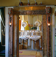 View through rustic oriental style doorframe into wood clad bathroom with twin enamel washbasins
