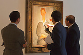 Pictured: Christie's Specialists are taking a close look at the painting Giovanotto dai Capelli Rossi 1919 by Modigliani. Estimated to fetch $8-12 million.<br /> <br /> Christie's London unveils touring highlights from the New York &quot;Impressionist &amp; Modern Art Evening Sale&quot; which are on free public view from 28 March to 1 April, ahead of the auction in New York on 6 May 2014.