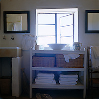 Painted wooden shelves have wicker baskers for storage in this simple rustic bathroom