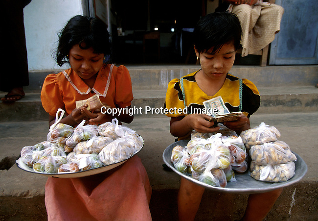 Two girls counting money as they are selling fruit and nuts on December 22, 1996 on a street corner in central Rangoon (Yangon) , Burma. They country is ruled by a military government who took power after they annuled democratic elections in 1988..(Photo: Per-Anders Pettersson/ Liaison Agency)