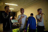 Jeppeson rests his hand on his chest while singing along to a video game in the teen activity room at the Citykirken Pentecostal church in Aarhus, Denmark. Jeppeson volunteers in the LOUD program at the church as a mentor for young teens.