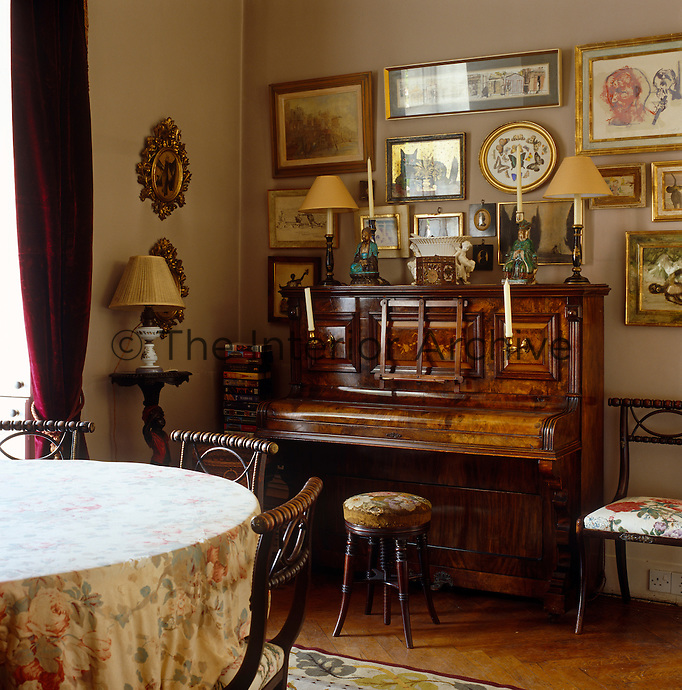 A piano in the corner of the dining room is surrounded by a collection of framed paintings