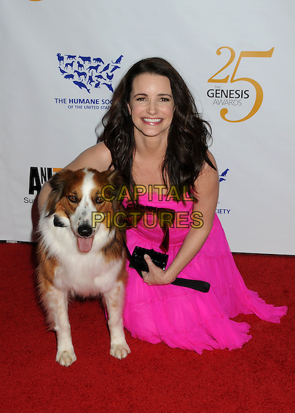 KRISTIN DAVIS .25th Anniversary Genesis Awards held at the Hyatt Regency Century Plaza, Century City, California, USA, .19th March 2011..full length pink dress dog pet animal bending half down bow kneeling .CAP/ADM/BP.©Byron Purvis/AdMedia/Capital Pictures.