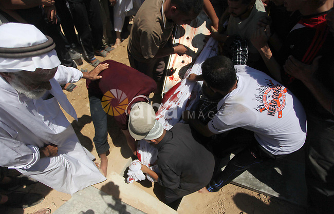 Palestinians bury the body of Ahmed Al-Masri, 14, who witnesses said was killed in an Israeli airstrike, during his funeral in Deir Al-Balah town in Central Gaza Strip, August 10, 2014. Palestinian negotiators will remain in Cairo for an urgent meeting with the Arab League on Monday to discuss the Gaza crisis, Egypt's state MENA news agency said. The Palestinian delegation had said it was likely to abandon Egyptian-mediated talks on Sunday unless Israel agreed to return to the table without pre-conditions. Photo by Ashraf Amra