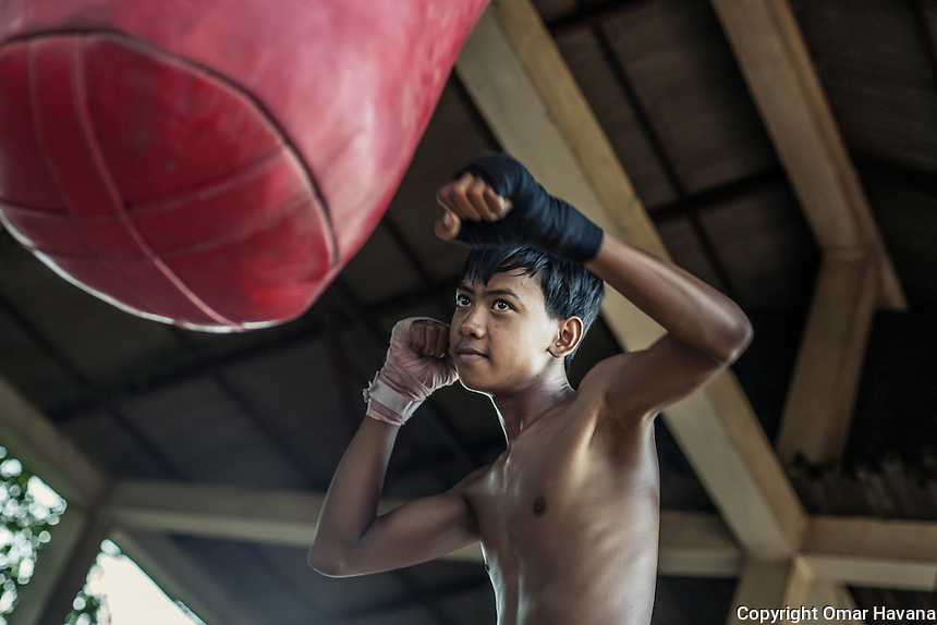 SIEM REAP, CAMBODIA. A young Kun Khmer fighter trains in Siem Reap, Cambodia. The average age of most Cambodian boxers is between ages 14 and 25. Pradal Serey or Kun Khmer -free fighting- is an unarmed martial art from Cambodia. Compared to other forms of Southeast Asian kickboxing, Kun Khmer emphasises more elusive and shifty fighting stances. The Cambodian style tends to utilise more elbows than that of other regions. Evidence shows that a style resembling pradal serey existed in the 9th century, leading the Khmer to believe all Southeast Asian forms of kickboxing started with the early Mon-Khmer people. They maintain that Pradal Serey has influenced much of the basis of Muay Thai. During the Khmer Rouge genocide, traditional martial arts were banned and many boxers were executed or worked to death, which nearly caused the death of pradal serey. Nowadays, Kun Khmer is making a strong comeback in Cambodia, with fighters attempting to market their style of boxing at the same caliber of Muay Thai. Photography: ©Omar Havana