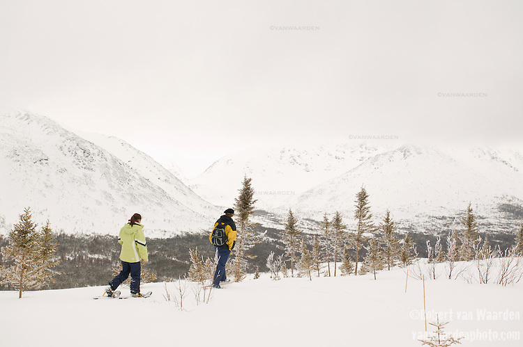 A man and a woman snowshoe across the snow covered landscape of the Chic Choc mountains in the Gaspe, Quebec, Canad