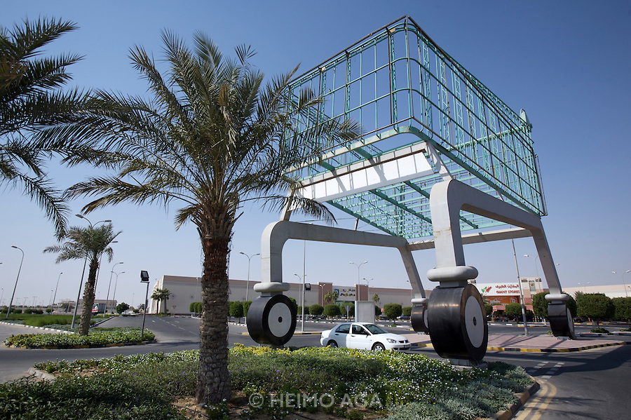Giant shopping cart at a supermarket parking lot.