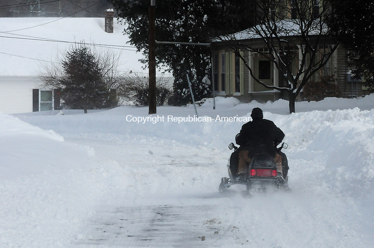 THOMASTON CT, 09 FEB 13-020913AJ12- A man drives a snowmobile down Elm Street in Thomaston Saturday morning.   Alec Johnson/ Republican-American