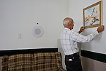 """Aug 10, 2008 -- COLORADO CITY: JOSEPH JESSOP, 86 years old, the patriarch of the Jessop family, arranges pictures on the wall in the living room of his Colorado City, AZ, home. The Jessops are polygamists and members of the FLDS. Colorado City and neighboring town of Hildale, UT, are home to the Fundamentalist Church of Jesus Christ of Latter Day Saints (FLDS) which split from the mainstream Church of Jesus Christ of Latter Day Saints (Mormons) after the Mormons banned plural marriage (polygamy) in 1890 so that Utah could gain statehood into the United States. The FLDS Prophet (leader), Warren Jeffs, has been convicted in Utah of """"rape as an accomplice"""" for arranging the marriage of teenage girl to her cousin and is currently on trial for similar, those less serious, charges in Arizona. After Texas child protection authorities raided the Yearning for Zion Ranch, (the FLDS compound in Eldorado, TX) many members of the FLDS community in Colorado City/Hildale fear either Arizona or Utah authorities could raid their homes in the same way. Older members of the community still remember the Short Creek Raid of 1953 when Arizona authorities using National Guard troops, raided the community, arresting the men and placing women and children in """"protective"""" custody. After two years in foster care, the women and children returned to their homes. After the raid, the FLDS Church eliminated any connection to the """"Short Creek raid"""" by renaming their town Colorado City in Arizona and Hildale in Utah.     Photo by Jack Kurtz / ZUMA Press"""