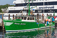 "Commercial fishing boat ""Miss Jenna"" docked next to a Seastreak ferry in Vineyard Haven Harbor, in Tisbury, Massachusetts on Martha's Vineyard."