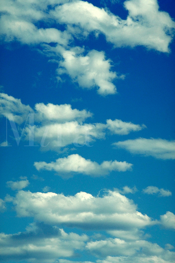 Soft, billowy clouds on blue sky. Airy, light, calm, serenity, serene. Connotations - Religious, power, new beginnings.