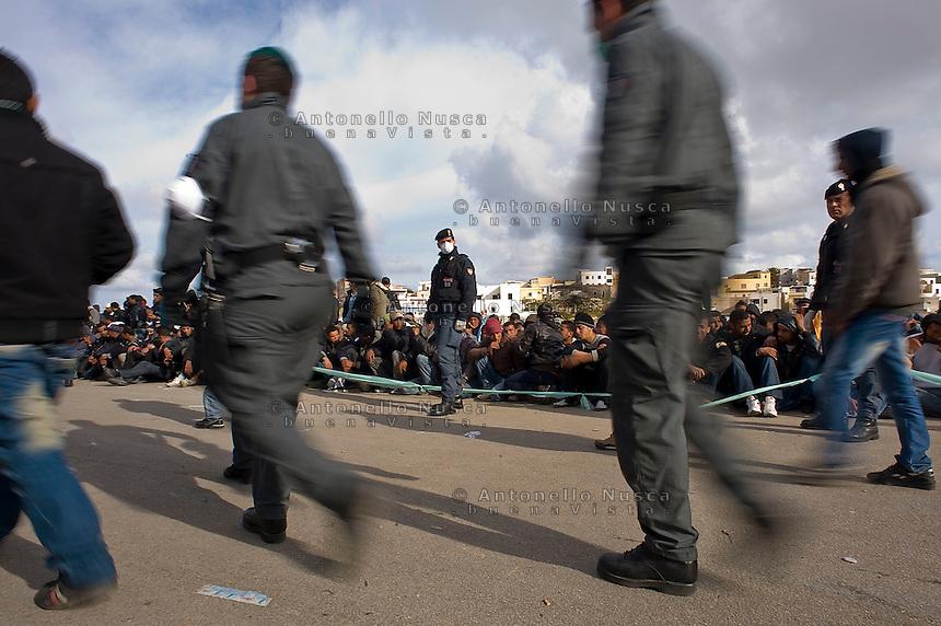Immigrati Tunisini vengono scortati dalla Polizia per l'identificazione prima di essere trasferiti nei centri di accoglienza. Tunisian immigrants are checked by Italian police before boarding a cruise liner to a different part of Italy, on the southern island of Lampedusa.