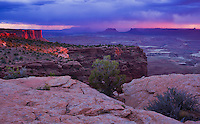 Canyonlands National Park, UT<br /> Sunset light illuminates the sandstone cliffs with storm clouds over the Green River Canyon from Grand View.