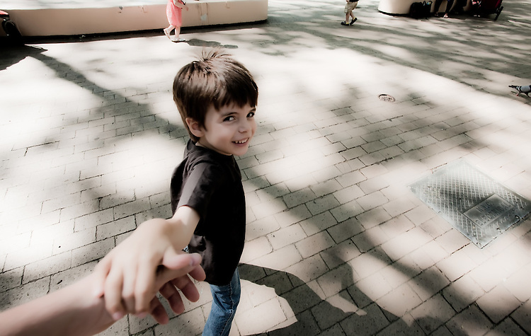 Little Boy running in a park holding his dads hand