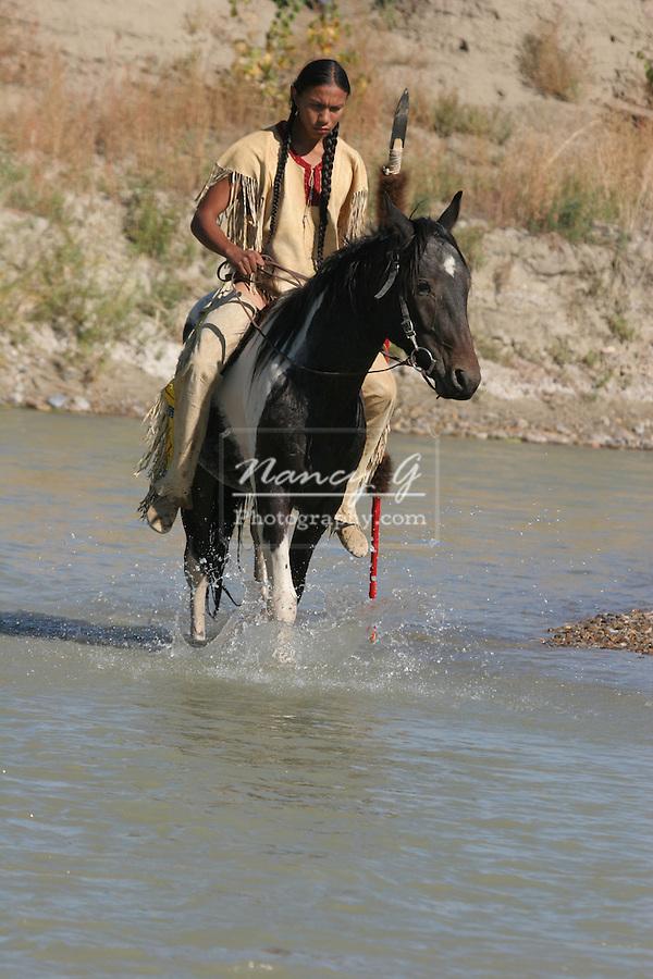 A Native American Sioux Indian boy on horseback riding across a stream in South Dakota