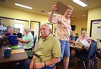 NWA Democrat-Gazette/DAVID GOTTSCHALK   Cindy Huffmaster (standing) grabs her husband Darrell's board Wednesday, July 12, 2017, after N 43 was called filling the spot during a game of blackout bingo at the Lowell Senior Activity Center. Bingo is played every Wednesday beginning at 9:15 a.m.. The center offers a variety of activities including Beanbag Baseball, Chair Yoga and musical entertainment.