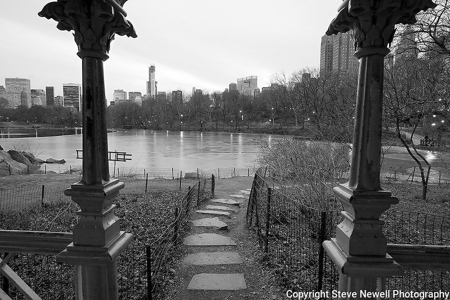 """The Ramble's Twilight"" Black and White Central Park New York. I shot this scene in the days before the worst storm in 20 years blew in on a Friday and lasted through Sunday.  The Governors in several states banned driving personal vehicles on the public highways for a couple days.  Being from Lake Tahoe I came prepared for the storm and was excited to capture New York City and Central Park with fresh snow.  The contrast of the abundant tall buildings surrounding Central Park was surreal. The loud noise of the city's activity was replaced with the solitude of nature inside the parks boundaries. The birds enjoyed the exposed water in the ice ponds and weren't bothered in sharing the experience with their human companions visiting the park for the day. Many families took to the park to play in the fluffy deep fresh snow with sleds for the hills and entertaining snow ball battles. I still found myself at times insulated from the park visitors and the bustling city by the absolute quietness nature offers in the isolated mountains of  my home town. Black and white photography is still my favorite so you will see many images offered in Color and BW."