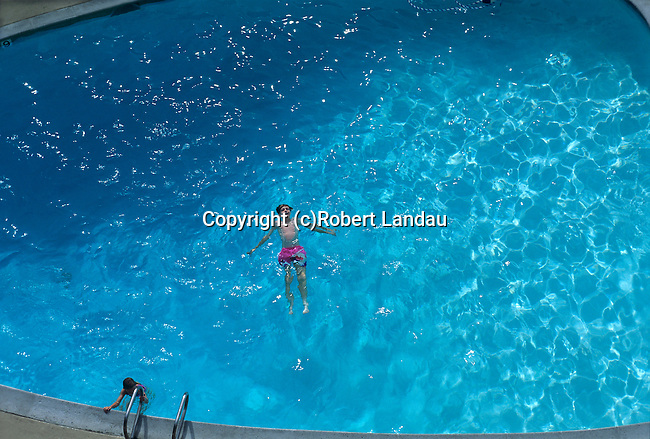 Boy Floating in Pool