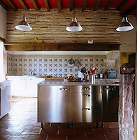 A contemporary stainless steel kitchen has been created within the original rustic framework of the house