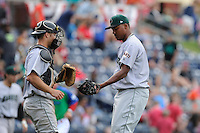 Relief pitcher Raymundo Montero (45) of the Augusta GreenJackets, right, gives the winning ball to catcher Jared Deacon after a save in a game against the Greenville Drive on Sunday, April 12, 2015, at Fluor Field at the West End in Greenville, South Carolina. Augusta won, 2-1. (Tom Priddy/Four Seam Images)