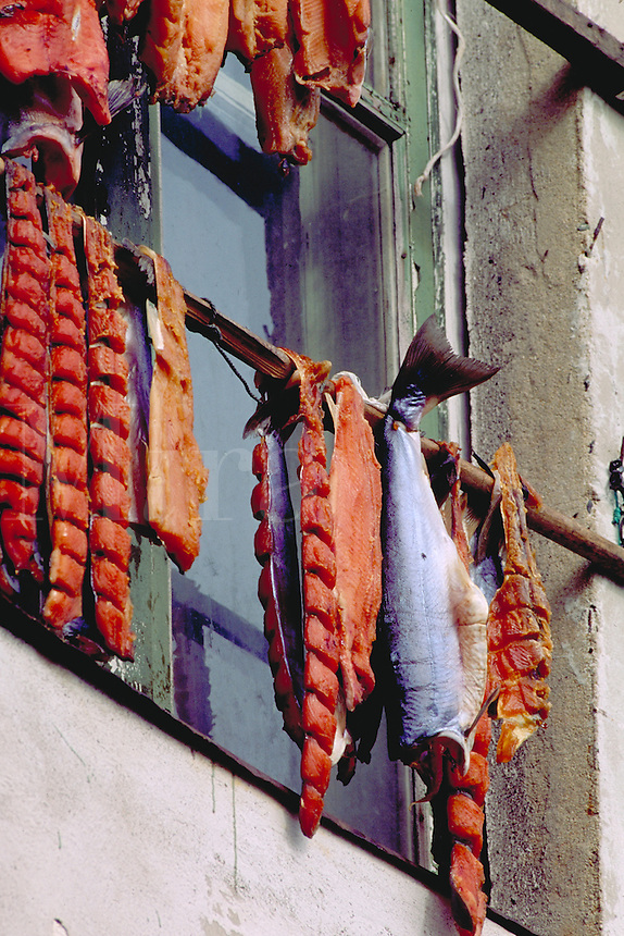 Salmon hang outside to dry on the wall of a wooden home, food, fish. Inchoun Village Siberia Russia Village on the shore of the Arctic Ocean.
