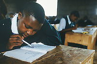Kenya. Rift Valley Province. Nyahururu. Classroom at Munyaka secondary school. A student listens to his teacher's lesson. His notebook is laid on a wood desk . The girl is wearing a green uniform. © 2004 Didier Ruef