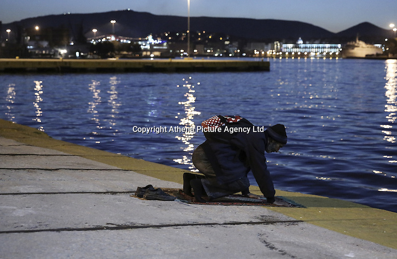 Pictured: A Muslim migrant man kneels down to pray minutes after he arrived at the port  Monday 22 February 2016<br /> Re: Thousands of migrants, most from Syria, have landed to the port of Pireaus, after crossing the border from Turkey to various islands like Lesvos and Kos in Greece.