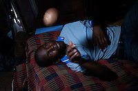 Ivan Matovu, 13, lies on his bed and plays with a baseball ball in his home at Kyambogo University sports ground, Uganda on July 28 2011. Ivan is the starting pitcher for Rev. John Foundation Little League baseball team.