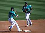 Seattle Mariners' Shawn O'Malley and Robinson Cano turn a double play against the SF Giants in a spring training game in Peoria, Ariz., on Wednesday, March 16, 2016. <br />