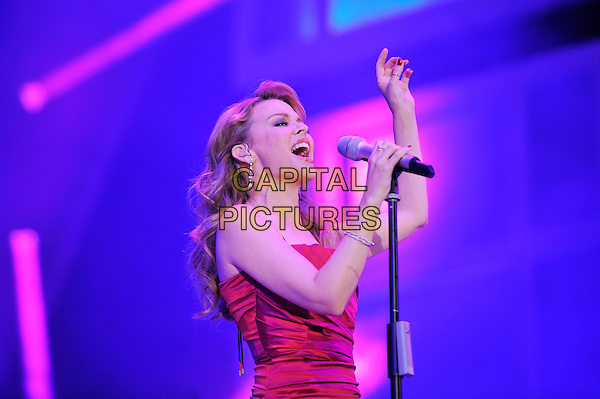 Kylie Minogue.performing at BBC Proms In The Park, Hyde Park, London, England, UK .8th September 2012,.on stage live concert gig half length  red dress ruched silk satin  singing microphone  hand .CAP/MAR.© Martin Harris/Capital Pictures.