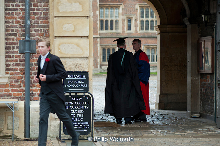 Two teachers in gowns at the entrance to Eton College.