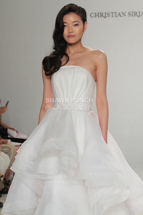 Model walks runway in a cascading strapless overlay gown, from the Christian Siriano for Kleinfeld bridal collection, at Kleinfeld on April 18, 2016 during New York Bridal Fashion Week Spring Summer 2017.