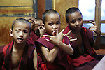 Young Buddhist monks in classroom with signs picked up from TV at Nalanda Buddhist Monastery, Punakha, Bhutan..Bhutan the country that prides itself on the development of 'Gross National Happiness' rather than GNP. This attitude pervades education, government, proclamations by royalty and politicians alike, and in the daily life of Bhutanese people. Strong adherence and respect for a royal family and Buddhism, mean the people generally follow what they are told and taught. There are of course contradictions between the modern and tradional world more often seen in urban rather than rural contexts. Phallic images of huge penises adorn the traditional homes, surrounded by animal spirits; Gross National Penis. Slow development, and fending off the modern world, television only introduced ten years ago, the lack of intrusive tourism, as tourists need to pay a daily minimum entry of $250, ecotourism for the rich, leaves a relatively unworldly populace, but with very high literacy, good health service and payments to peasants to not kill wild animals, or misuse forest, enables sustainable development and protects the country's natural heritage. Whilst various hydro-electric schemes, cash crops including apples, pull in import revenue, and Bhutan is helped with aid from the international community. Its population is only a meagre 700,000. Indian and Nepalese workers carry out the menial road and construction work.