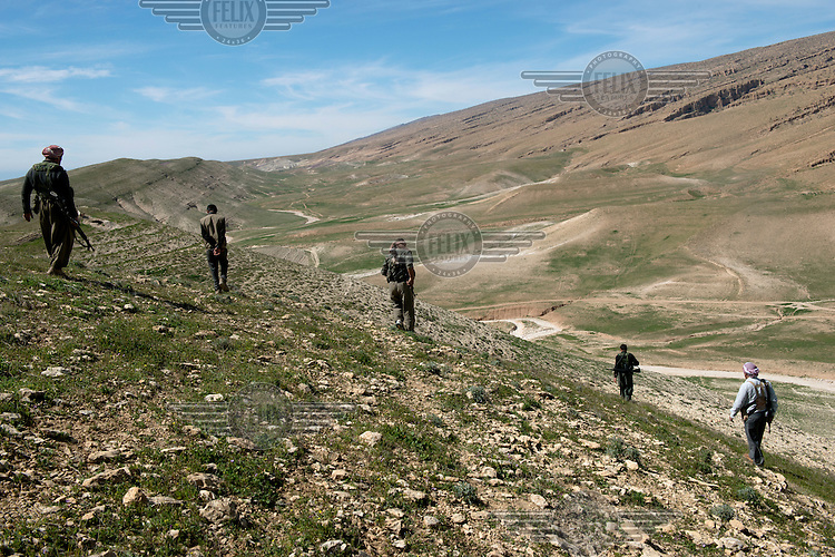 Yazidi fighters walk across an arid mountainside in the Sinjar mountains. Around 1,000 Yazidi men who used to be teachers, civil servants and other professions have become fighters since August 2014 when Islamic State (IS) fighters attached Yazidi towns and villages. They are now based in a camp in the mountains. <br /> <br /> Thousands of Yazidis fled to the mountains when Islamic State (IS) fighters attacked towns and villages around Sinjar in August 2014. Since then Yazidi refugees have been living in precarious conditions with no electricity or running water and children haven't been attending school. Support from the international community has been insufficient and people are dying of hunger and disease. Until December 2014 the mountains were surrounded by IS. Now the southern part of the mountains is still under IS control.