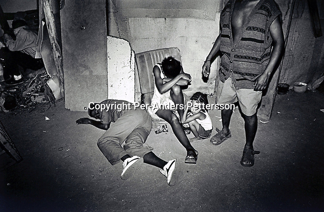 UPINGTON, SOUTH AFRICA - FEBRUARY 9: A drunk man has passed out on the ground, while his family is sitting next to him in a illegal bar on February 9, 2002 in Loisevale near Upington, South Africa. Loisevale, a poor and destitute colored/black township where unemployment is high, and a number of social problems including domestic violence and alcohol abuse. Baby Thsepang, an 8-month old baby was raped by her father in a house on this street in October 2001. The baby rape shocked the country, and it is struggling with an increasing number of rapes and sexual abuse of young children. The country has the highest number of rapes in the world..Photo: Per-Anders Pettersson/ Agentur Focus...