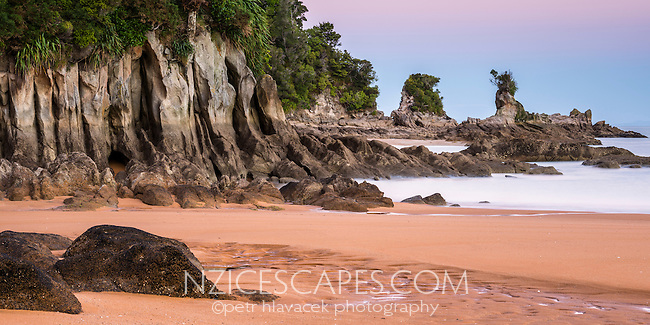 Coastal rock formations under pastel colours of twilight after sunset on Totaranui beach on Abel Tasman Coast Track, Abel Tasman National Park, Nelson Region, South Island, New Zealand