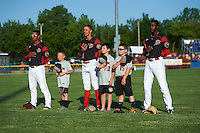 "Batavia Muckdogs players including Jhonny Santos (32), Corey Bird (12) and Isaiah White (18) stand with the ""Stars of the Game"" for the national anthem before a game against the State College Spikes on June 24, 2016 at Dwyer Stadium in Batavia, New York.  State College defeated Batavia 10-3.  (Mike Janes/Four Seam Images)"