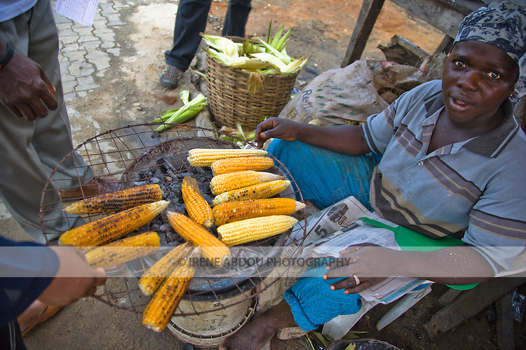 A woman grills corn on the side of the street to sell to passersby in Lagos, Nigeria.