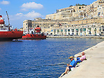 Men fishing historic waterfront buildings on quayside, Valletta, Malta