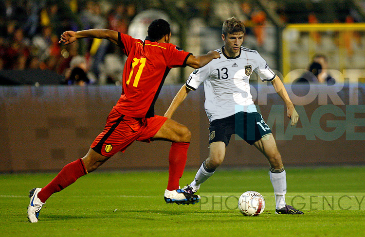 Thomas Mueller of Germany takes on Moussa Dembele of Belgium
