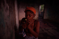"""Rosetta, 22 years old, lights up a marijuana cigarette stump while doing drugs in an abandoned compound  in Monrovia, Liberia on  Wednesday March 21 2007..Melvin, 29 AKA """"Dad"""",  John, 29 AKA """"Desperate Soldier, Thomas 28 AKA """"Bullet Patrol"""", Leroy, 28, AKA """" Pussy Mechanic"""" and Steven 27 AKA """"Field Marshall"""" are all former child soldiers that found each other on the streets after the last round was fired in Liberia. Since then they """"Hustle"""" to put some food in their stomachs and buy some drugs to """" make them forget about their lives""""..ALL NAMES HAVE BEEN FICTIONALIZED TO PROTECT THE IDENTITIES OF THE 5 MEN."""