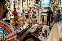 Father Rick Frechette led the daily prayer service in the small stone chapel beside St. Damien Children's Hospital on November 20, 2017 in Port-au-Prince, Haiti. 3 cardboard caskets lay on the floor below the altar. These were the hospital patients who died the night before. Inside the caskets were babies, their bodies wrapped in colored paper, their names printed on the binding masking tape. <br /> Father Frechette read each name aloud during the service, and later, the small congregation held hands around the bodies.<br /> Photo Daniel Berehulak for The New York Times