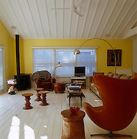 The living room with painted white floorboards and yellow walls is furnished with modern pieces in warm tones