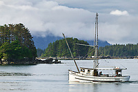 Commercial trolling vessel crosses Sitka Sound with the Rockwell Lighthouse in the distant islands, Coastal town of Sitka, Alaska