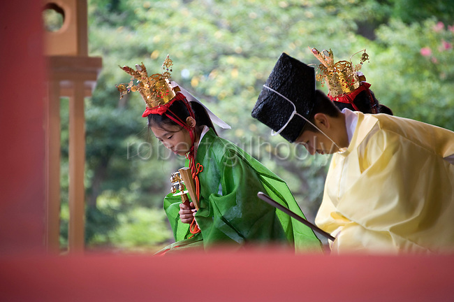 A yaotome performer bows alongside a priest prior to a traditional dance at Tsurugaoka Hachimangu shrine during the second day of the 3-day Reitaisai grand festival in Kamakura, Japan on  15 Sept. 2012.  Photographer: Robert Gilhooly