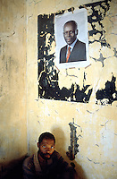 Angola. Cuando Cubango. Mavinga. Man seated on the floor in a hospital run by MSF (M?decins Sans Frontires) Switzerland. The poster on the wall is a picture of Mr. Jos? Eduardo dos Santos, the current president of Angola. © 2002 Didier Ruef